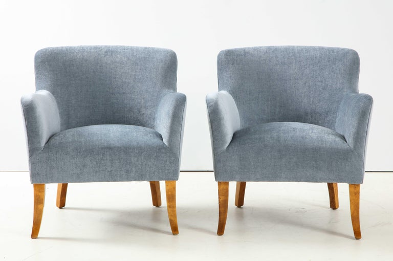 A pair of Swedish upholstered club chairs, circa 1940s, with rectangular and curved back, tight seat and curved armrests raised on Birchwood outplayed sabre legs.