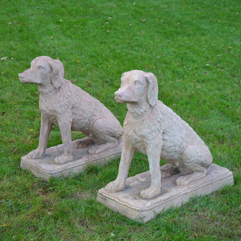 A pair of seated terracotta spaniels, both with proper right front paws forward, one with head straight on, the other with head slightly turned to the left, attributed to Moorhead Clay Works, Philadelphia, circa 1890. Measures: 29 ins. high, 13.5