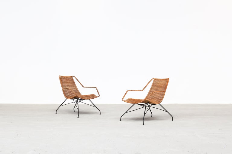 A beautiful pair of unique lounge chairs by Carlo Hauner & Martin Eisler manufactured in Brasil. Both chairs come with a light metal frame and a rattan mesh in a very good condition. Ready for usage.