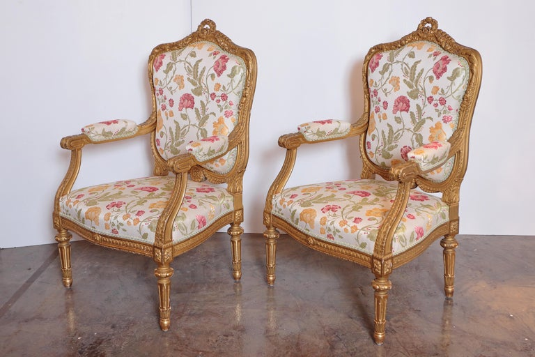 A pair of early 20th century French gilt carved fauteuils. Fine quality gilt carving. Covered in a Scalamandre fabric.