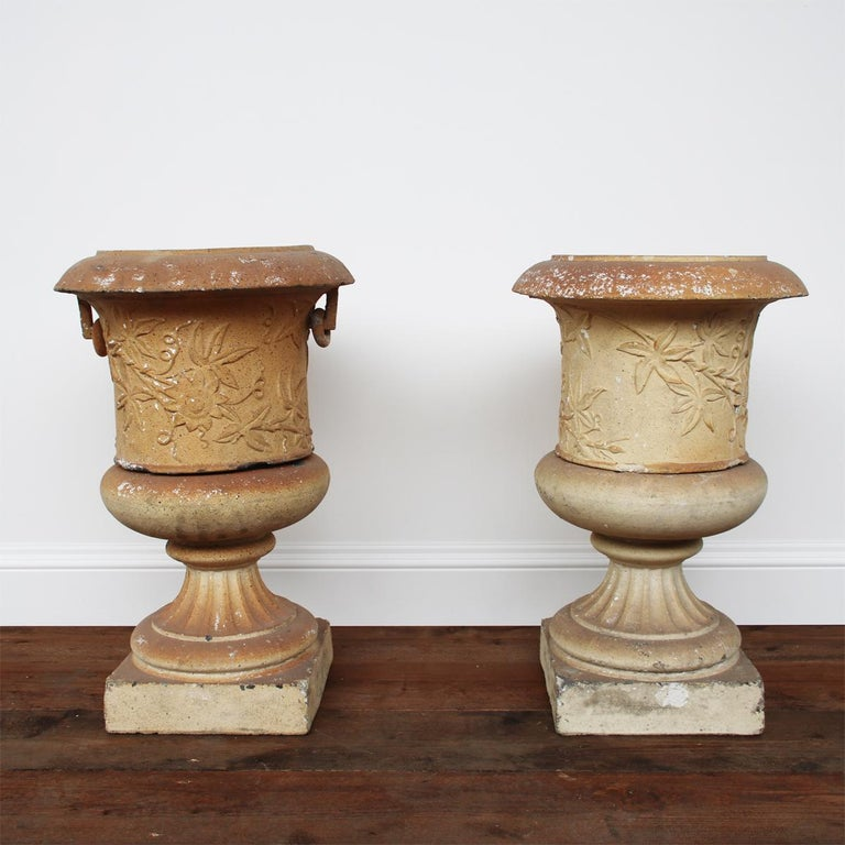 A pair of Victorian clay garden urns on pedestals by the Garnkirk Fireclay Company of Lanarkshire, decorated with a continuous band of passion flowers. One urn is missing its ring handles.