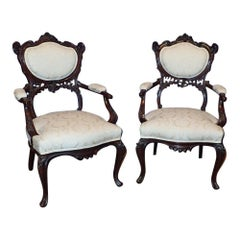 A pair of Victorian Rococo Carved Arm Chairs