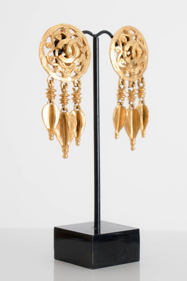 A pair of 1995 Chanel gold toned clip-on earrings with a round ornamental base with a Chanel double 'C' logo in the centre. Three beaded strands hang from the base.    The earrings are stamped: Chanel, 95, A, Made in France  The earrings meassure: