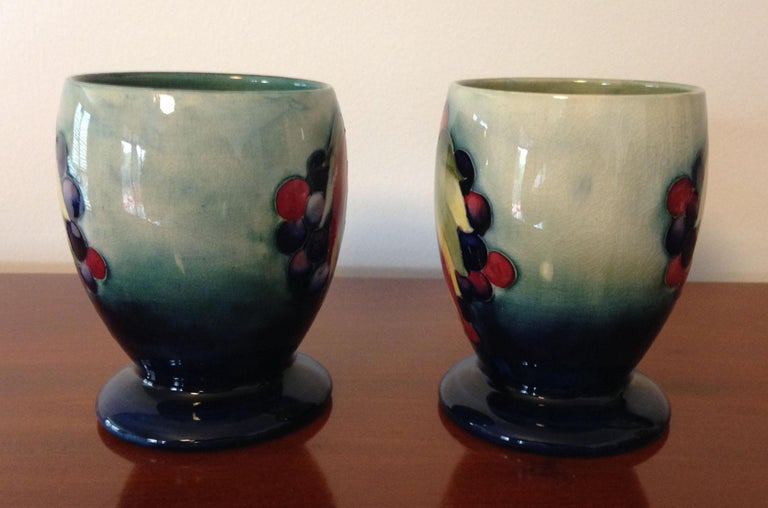 A rare pair of William Moorcroft designed leaf and berry pattern goblets with a pale blue/green background, circa 1930.
