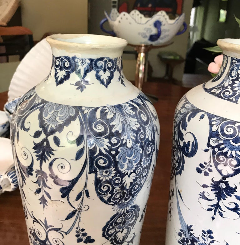 Two delft vases late 18th-early 19th century produced in the Dutch region off delft in the Netherlands Minor old restorations on the top No cracks Marks on the bottom Beautiful and many different flower patterns on both vases.