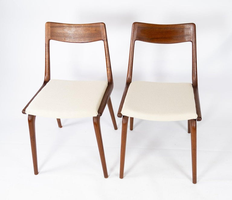 A papir of dining chairs, model Boomerang, in teak and light wool fabric designed by Alfred Christensen from the 1960s. The chairs are in great vintage condition.