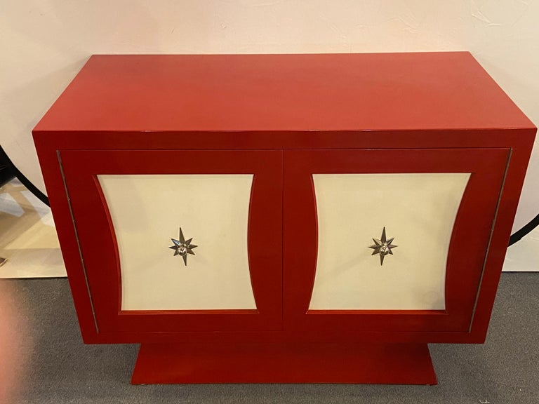 A Parzinger style cabinet, commode or server lacquered in red and white A two-door fire-engine red and white lacquered Parzinger style cabinet. The stylish Mid-Century Modern cabinet features three custom fitted interior drawer. This cabinet,