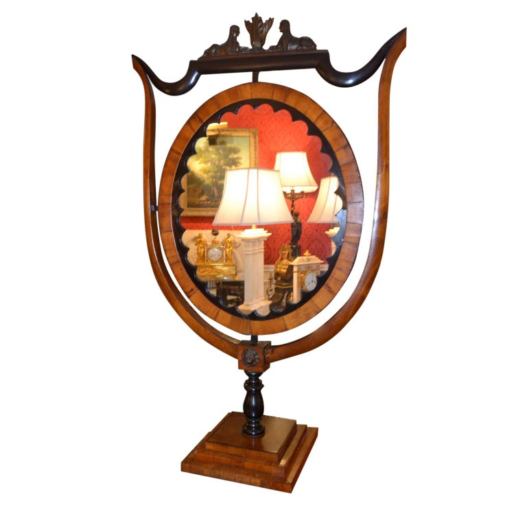 A rare Biedermeier standing table mirror in ebony and fruitwood. The shield shaped frame is supporting an oval mirror surmounted by two facing ebonized Egyptian sphynx. The whole is supported on a stepped rectangular base. It does not swivel.
