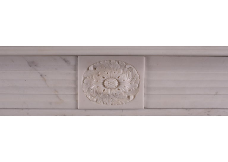 A period English Regency fireplace in statuary marble. The jambs with half rounded reeds surmounted by roundel end blockings. Carved central paterae to frieze, English, circa 1820. One of a very near pair with stock no 3961.