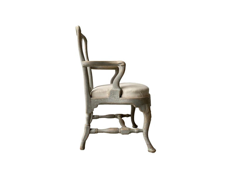 A period Swedish Rococo armchair with decorative carved shell detail in the back and seat stretcher. This piece has been repainted in light greenish grey and the seat has been reupholstered.