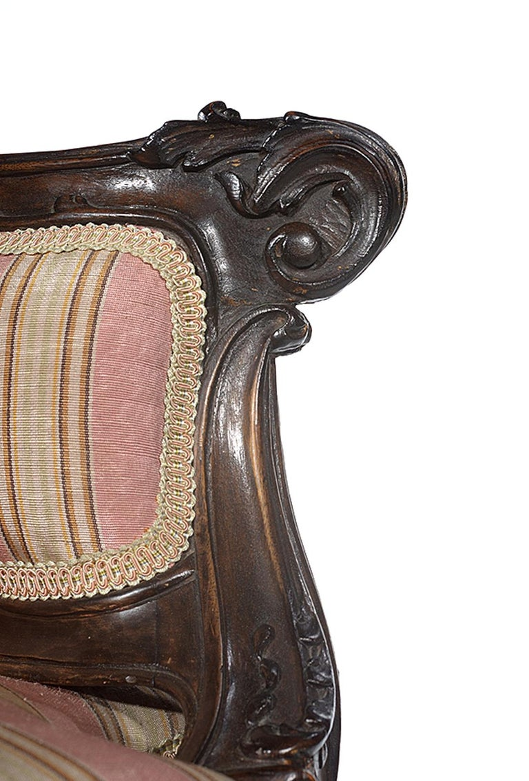 The walnut frame with carved acanthus leaves and bell flowers, the back, side panels and seat all upholstered in a pink and cream striped fabric.