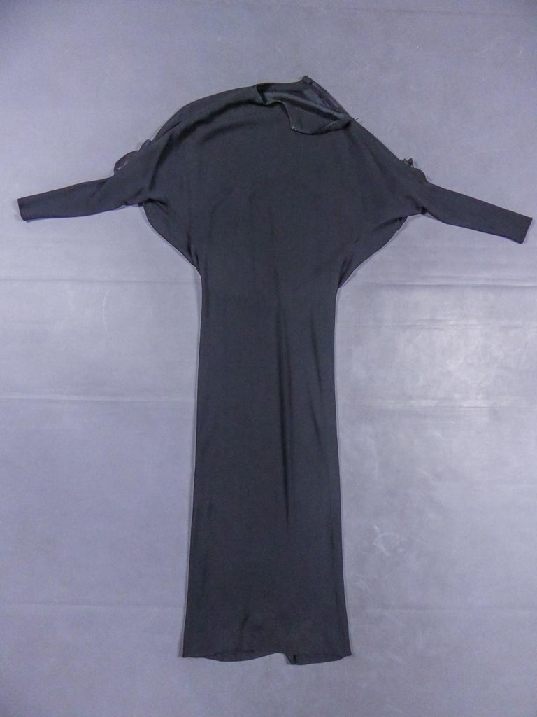 Circa 1976/1978  France  Beautiful evening dress Pierre Cardin Haute Couture in black silk jersey dating from the late 1970s. Crew neck dress in stretchy black silk jersey, with long bat sleeves decorated with two flowers with black silk petals and