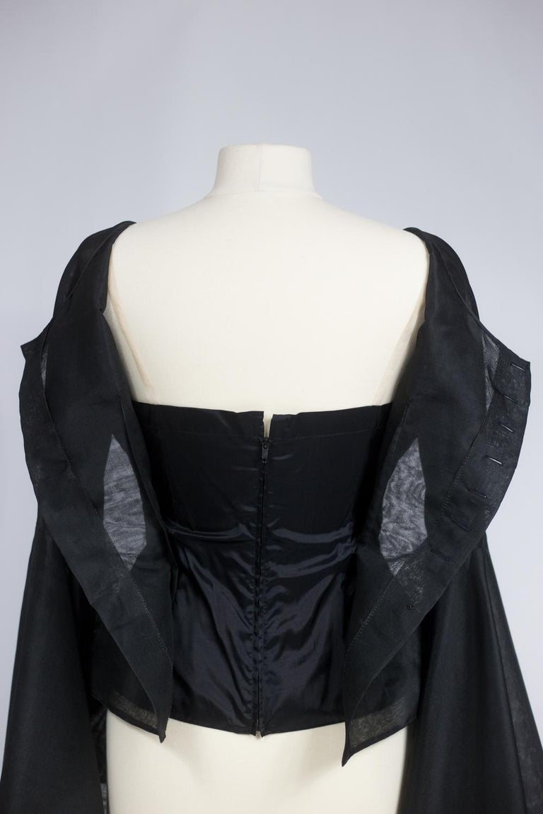 Circa 1970/1980  France  Stunning Blouse in black Organza by Pierre Cardin (attributed to) dating from the 1970s / 1980s. Boat neckline blouse buttoned in front and dramatic raging sleeves ending in gigantic pagodas, cut in the bias and rounded