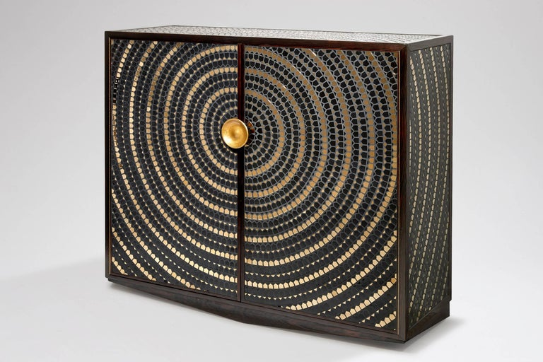 A pinewood cabinet veneered with a mosaic of black and gold ceramic. The doors open onto an inside in oak fitted with shelves. The handle in bronze.