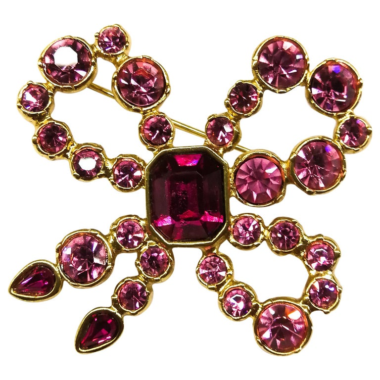 A pink paste and gilt metal 'bow' brooch, Yves Saint Laurent, France, 1980s For Sale