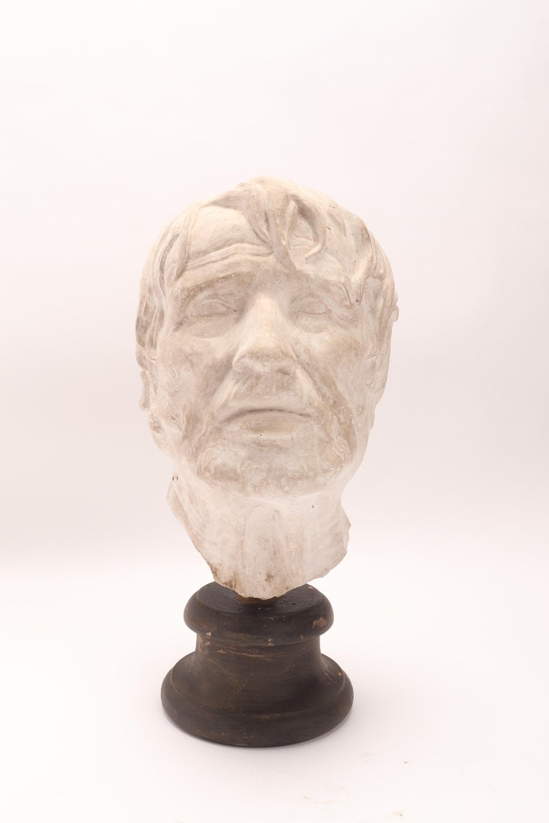 Over the wooden black painted base is set the plaster cast of the head of Seneca, from bronze from Ercolano, I Century a.C. The cast for drawing teaching in Academy. Italy circa 1890.