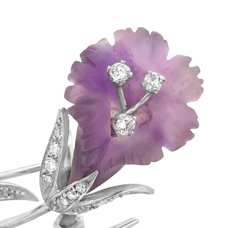 This artfully designed flora motif brooch is rendered in solid 18K white gold, consisting of a carved and frosted amethyst flower, one carved and frosted rock crystal leaf, four round brilliant cut diamonds weighing approximately 0.26 carat total
