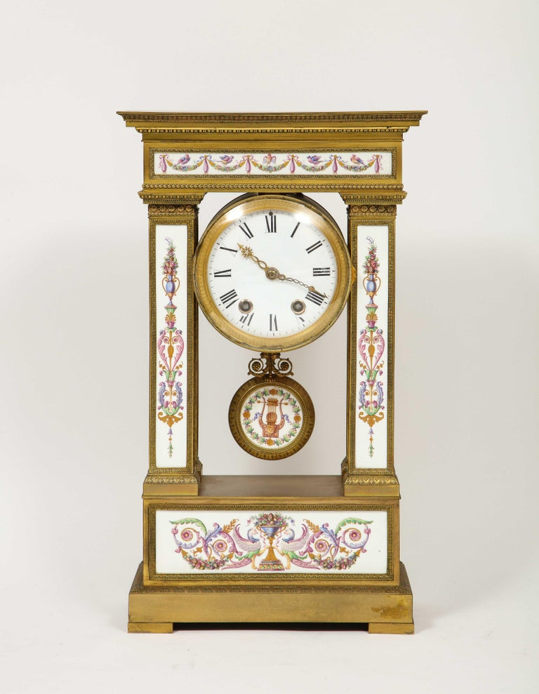 A Rare and Exquisite French Ormolu Bronze and Porcelain Clock, attributed to Jean Francois Deniere,  circa 1810.  This large and elaborate clock is made of the finest quality ormolu and porcelain during the period. Of rectangular form, with