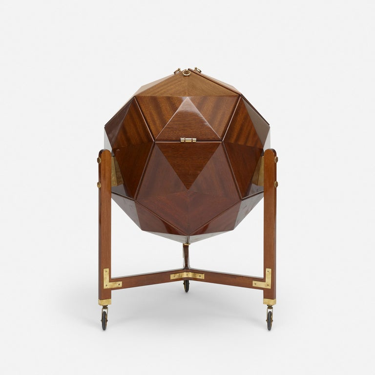 A rare and unusual polyhedron bar cabinet by M. Vuillermoz  Dambrine France, circa 1960 mahogany, brass  Three mahogany doors lined in brass open to reveal storage for bottles and barware.  Doors are fitted with brass ring pulls.   Legs