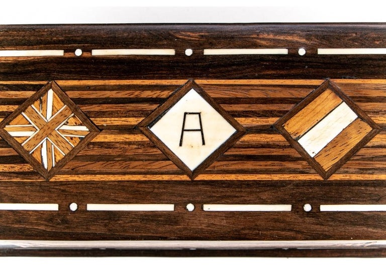 """An exotic rectangular wood box with parquetry striped, square and diamond inlays and monogrammed center lid diamond with an """"A."""" Bone details. Double compartments inside. Leather bottom. The box has a very soft hand from a well crafted finishing of"""
