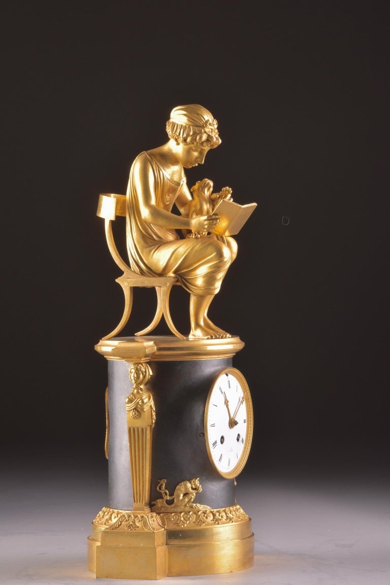 Exceptional beautiful rare French, ''Library'' in the style of Claude Galle (1759-1816). Dated circa 1810-1815. With the image of a young girl sitting at the stoel and reading a book, with her dog on her lap. The clock is further decorated with two