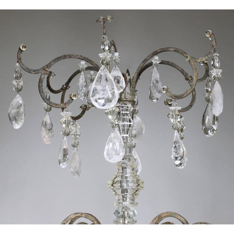 A rare French 19th-20th century Louis XV style six-light patinated metal and rock-crystal chandelier. The thin metal frame surmounted with six