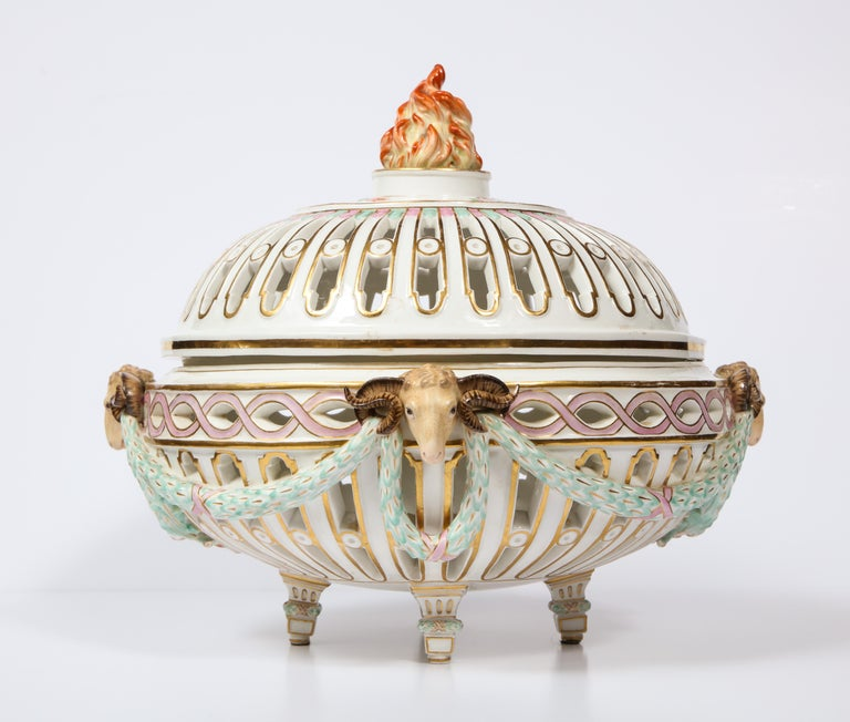 A large, beautiful, and rare 19th century neoclassical reticulated meissen centerpiece with open filigree, rams heads, flaming finial, and love bird cartouches. This exquisite Meissen centerpiece was made in arguably the height of Meissen Porcelain