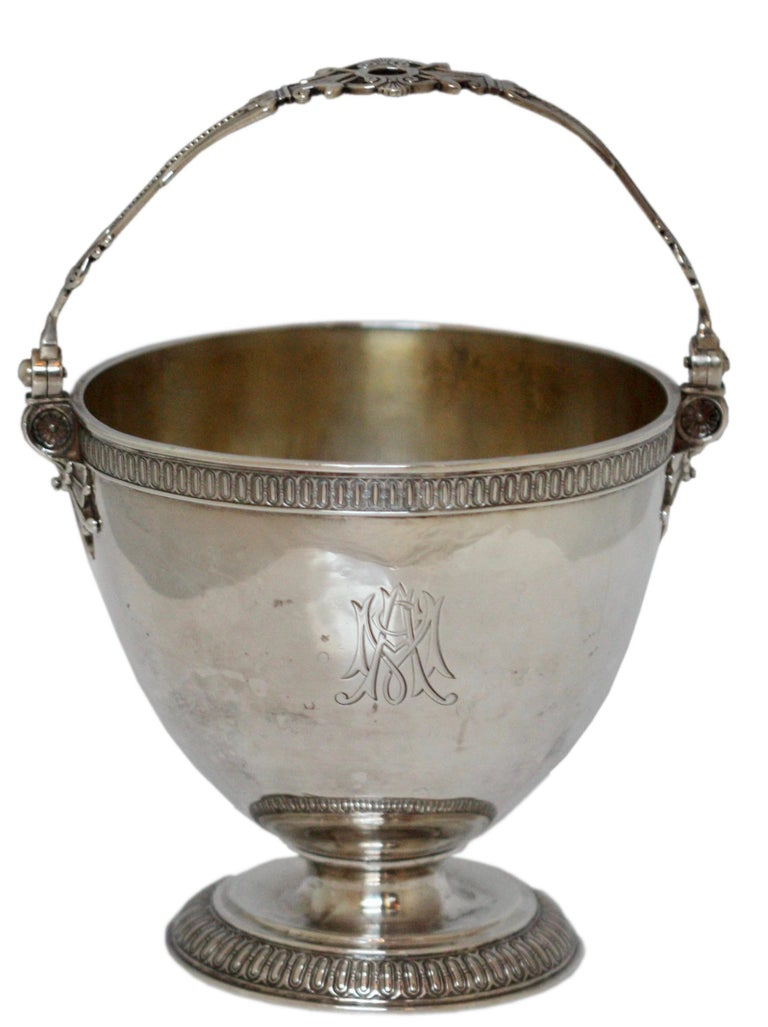 A rare Tiffany & Co. Sterling silver sugar bowl.  American, 1870-1875. Made for an International Exposition.  Of basket shape with swing handle, engraved with a conjoined monogram with guilloche borders on a circular foot. Diameter 4 1/2
