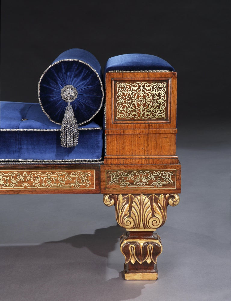A rare Regency period Divan after a design by Thomas Hope  Constructed in goncalo alves, rising from shaped, waisted short legs, part gilded, and carved with palmettes and lotus leaves, in the Graeco- Egyptian taste, the block ends and rails