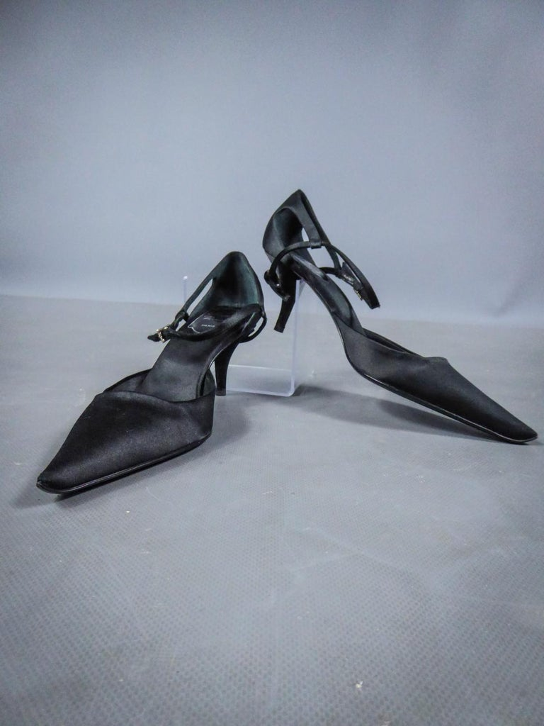 Circa 2000 France  Pair of evening pumps as new by Roger Vivier in black silk satin dating from the year 2000. Shoes with stiletto heel with pointed shape in front, decorated with a bow in the same fabric on the heel. Closes by a strap with a