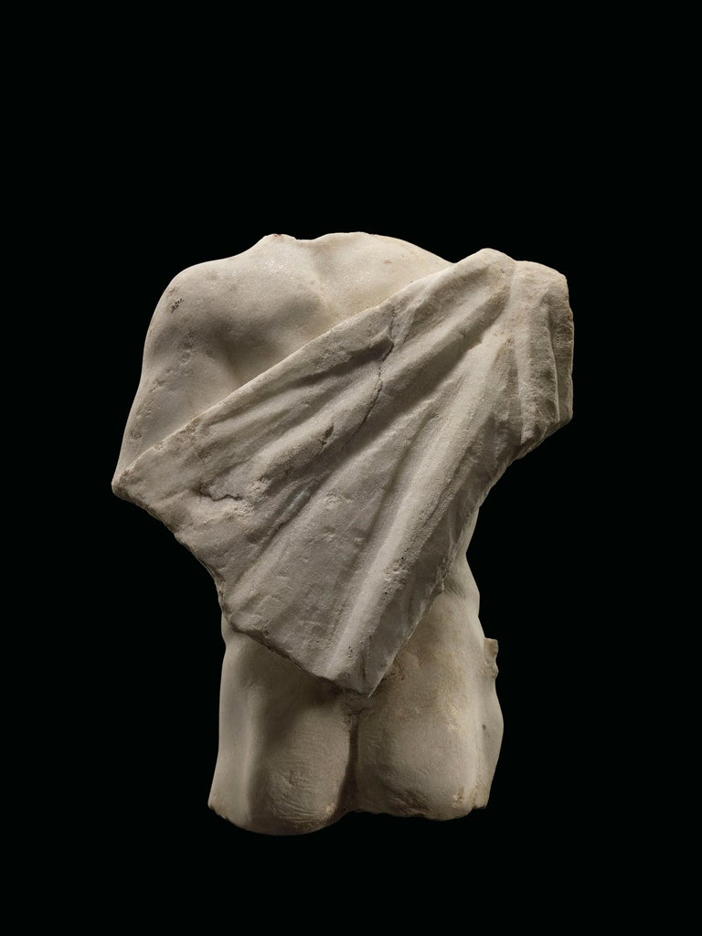 The figure rendered frontally in contrapposto, the remains of a cloak joined by a small support and draped over his right arm which was originally pinned, and diagonally over his back.