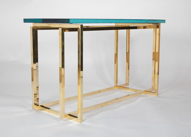 A custom made textured reverse painted glass top (Later) on a period brass console table designed by Romeo Rega. Please note blue appears slightly darker that it is in reality.