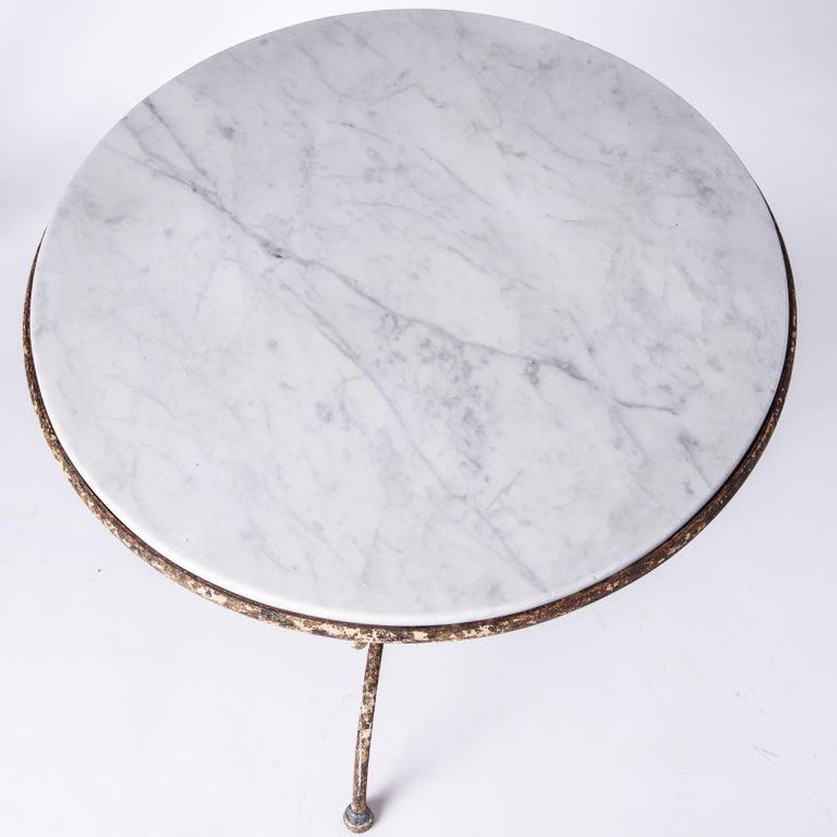 This charming table has a lovely piece of white marble set in the original antique wrought iron base. The base, with traces of old paint is curved and joined at the centre by a ring, ending in rounded feet, typical of the late 19th century.