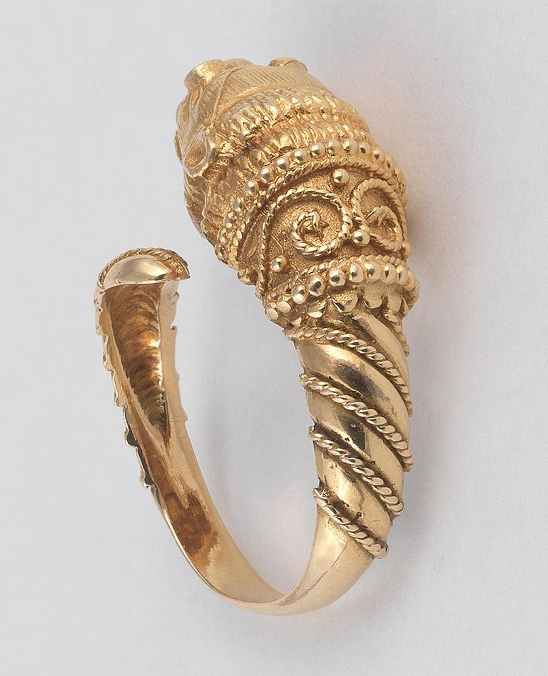 Realistically modelled as a lion's head, the eyes set with circular-cut rubies, the stylised body with ropetwist decoration, signed Ilias Lalaounis, maker's mark, ring size approx. 8