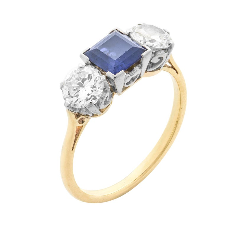A sapphire and diamond three stone ring, the square-cut sapphire weighing 0.98 carats, set between two round brilliant-cut diamonds, the one weighing 0.49 carats of F colour and SI2 clarity, the other weighing 0.46 carats of F colour and SI1