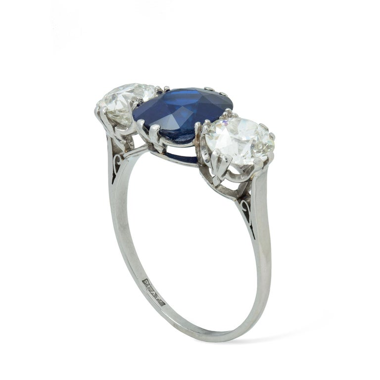 A sapphire and diamond three stone ring, the oval-cut sapphire weighing 3.13 carats, set between two round old-cut diamonds weighing 2.11 carats in total, set to a white claw collet to raised shoulders, stamped platinum, circa 1930, head measuring