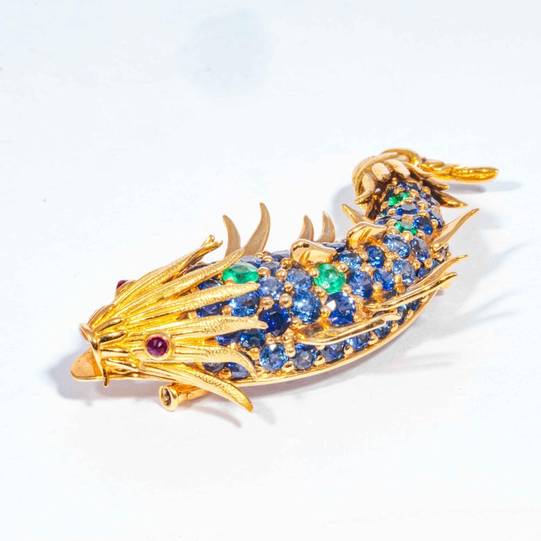 This late 20th century pin is comprised of full cut blue Ceylon sapphires, a 5 accenting green emerald fish