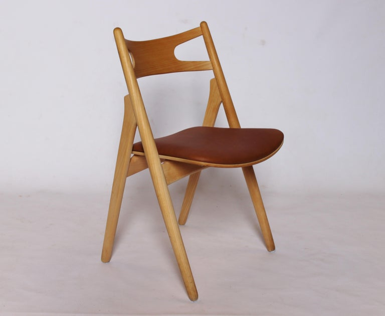 A Sawbuck chair, model CH29, designed by Hans J. Wegner in 1952 and manufactured by Carl Hansen & Son in the 1970s. The chair is made of soap treated beech and with seat of cognac elegance leather.