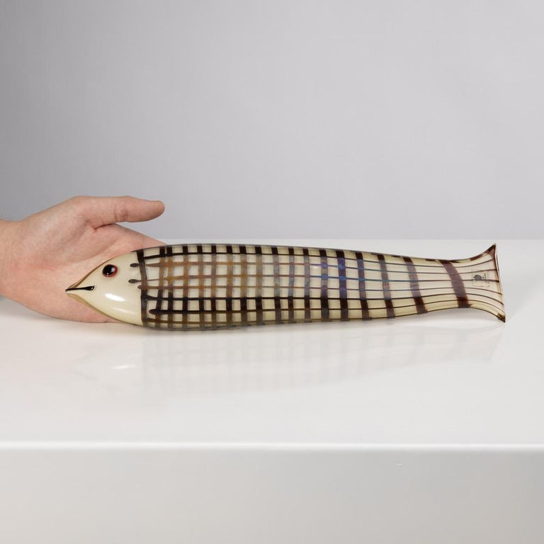 This large fish measures 36 centimeters long in opaque clear amber glass and decorated with a grid of dark amethyst glass. The detail of the black eye on a red background. Ken Scott wanted a slightly iridescent surface for this model.  This