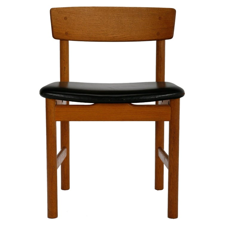 A large set of dining chairs in solid oak with a beautiful golden patina. Seats upholstered in original black leather. Designed in 1956 by Børge Mogensen for Fredericia Stolefabrik, Denmark