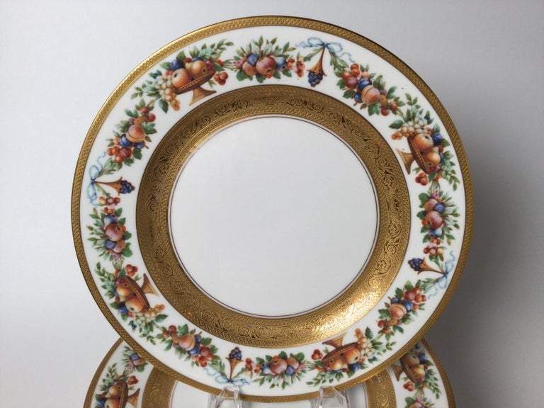 Set of 12 porcelain and gilt service plates. The decorative borders with swags and garlands of fruit with detailed gold bands on the edge and in the center.