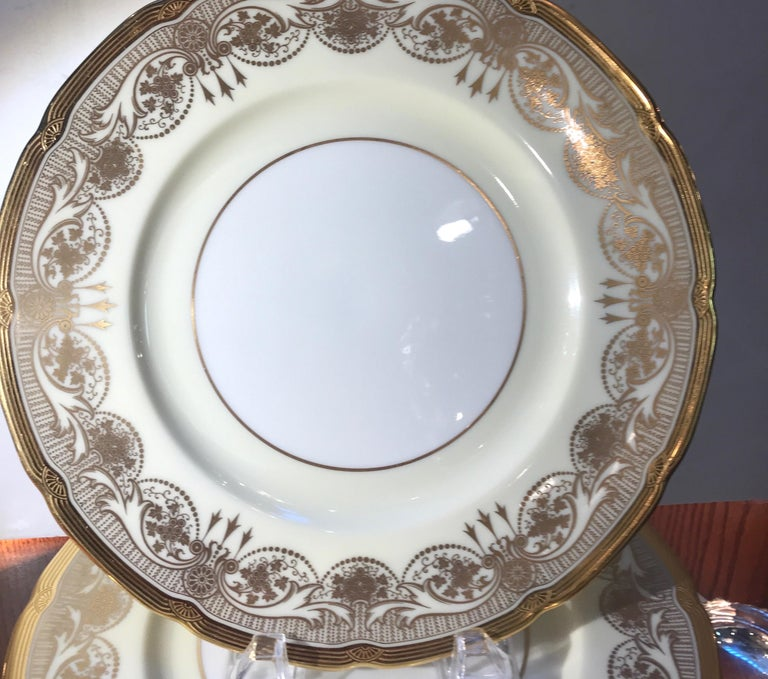 A Set of 12 elegant gold encrusted border dinner service plates. Each one with a fancy detailed gold border on a light vanilla cream background with an ivory white center. Marked on the back with an early Lenox green mark from 1930 or before. The