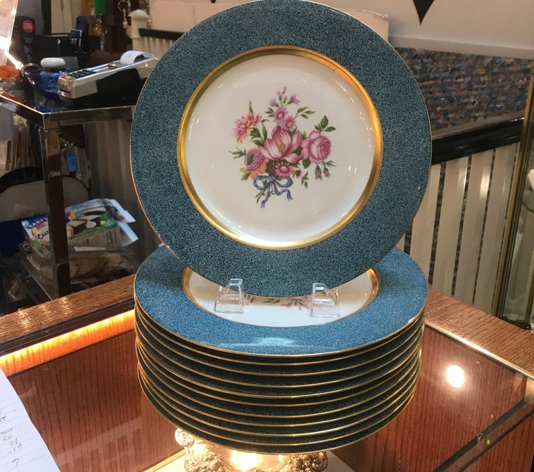 A set of 12 elegant floral service plates made by Theodore Haviland New York. The Dresden floral center with gold band with a hand stippled teal broad border. The mark is black and red, 1937-1956.