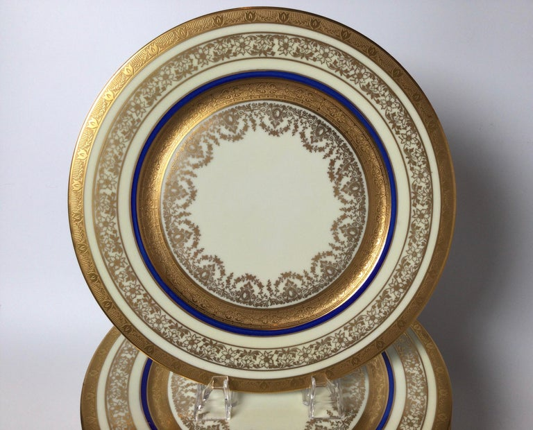 Elegant set of 12 gilt porcelain service plates with cobalt blue band. The several bands of gold with a thin cobalt band on a bone color porcelain plate. Retailed by Ovington Brothers, NYC.