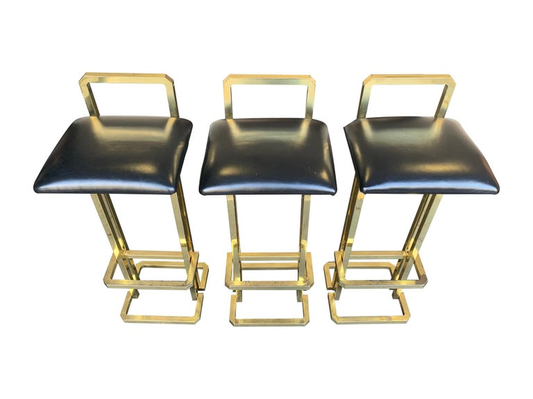 A set of 3 1970s Maison Jansen style gilt metal stools with black leather seat pads, each one has a back and foot rest.