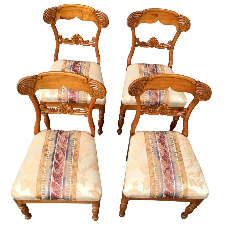 A set of 4 Swedish Biedemeier dining chairs in birch wood from circa 1820-1840. Lathed front legs, nice warm patina, plentiful carved back and removable sits.