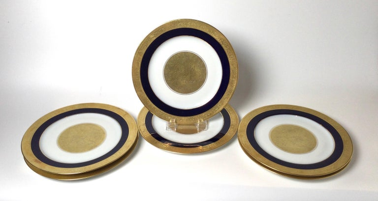 A set of 6 regal heavy gold and cobalt blue service plates. The outer broad band with cobalt band over white European porcelain with a central medallion depicting 18th century style courting couple. Measures: 10.75 inches in diameter.
