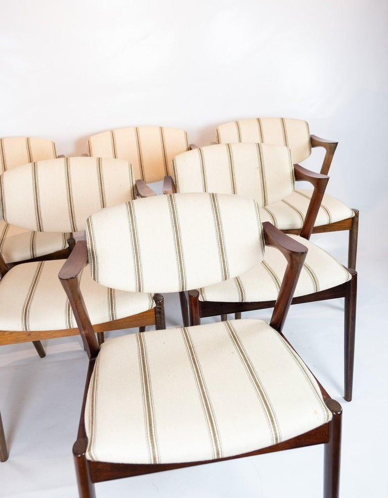 A set of 6 dining chairs, model 42, designed by Kai Kristiansen and manufactured by Schou Andersen in the 1960s. The chairs are of rosewood and upholstered in light wool fabric.