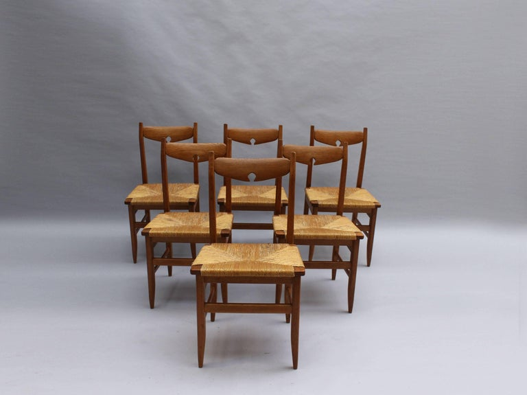 A set of six, French, 1960s oak and handwoven rush seat dining chairs by Guillerme et Chambron for Votre Maison (editor). A matching table is available (not included in price), see pictures.