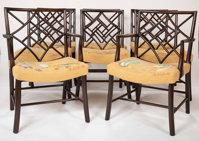 A set of 8 large Chippendale style dining chairs. Composed of 6 side chairs and two armchairs. Each chair has a different clean needlepoint design.